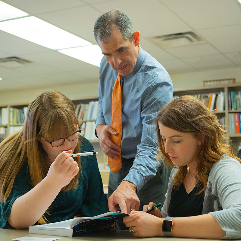 An agricultural education faculty member helping two students.