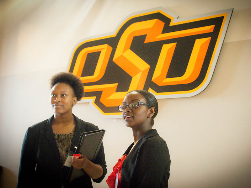Two women standing in front of the OSU logo.