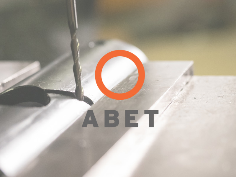 ABET logo with metal work happening in the background