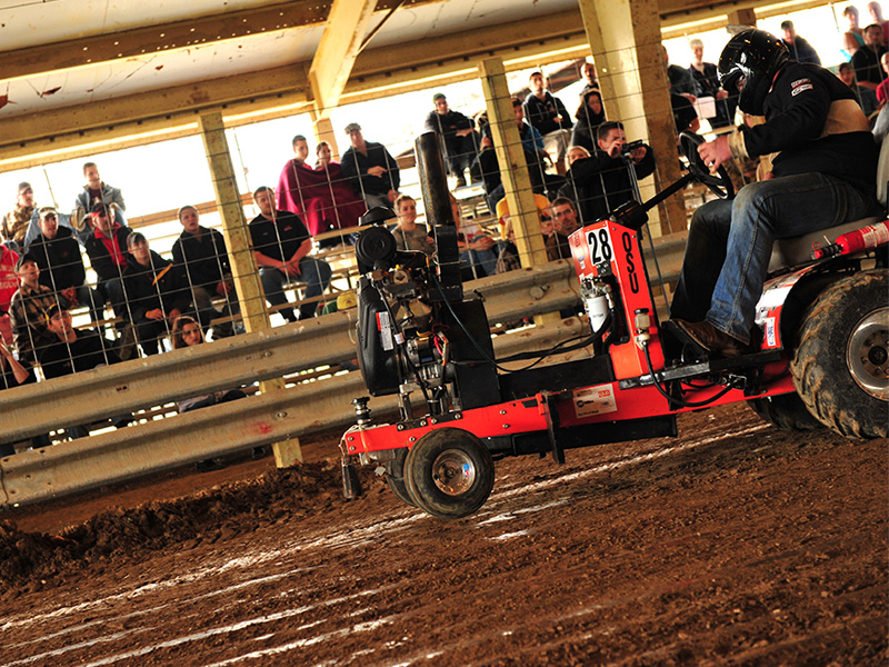 Cowboy Motorsports member drives the tractor students made for competition.