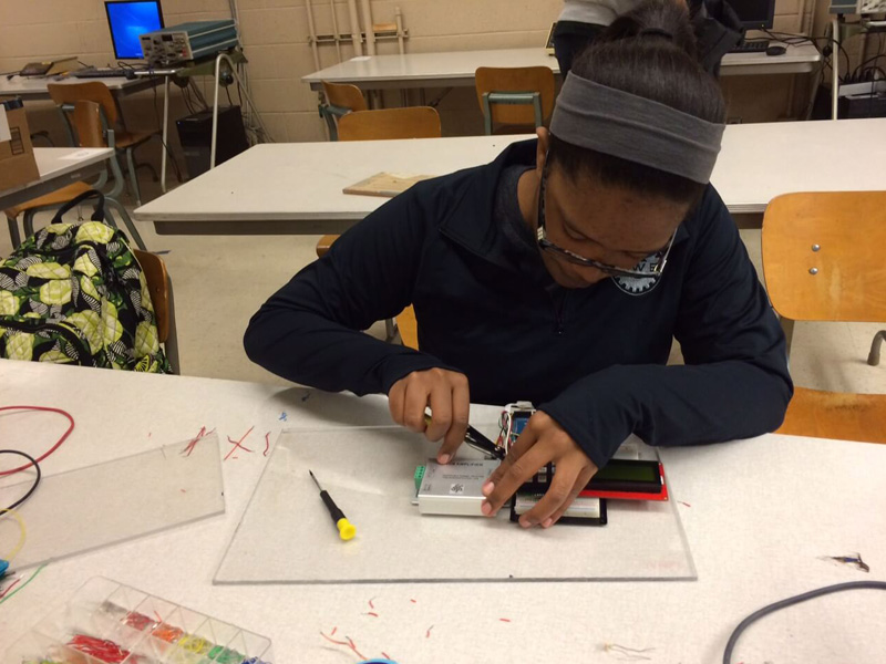 Sneior design student works on a programing board